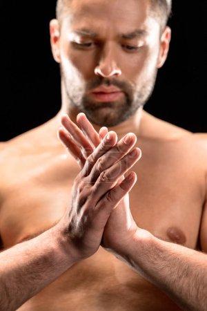 Shirtless man rubbing hands