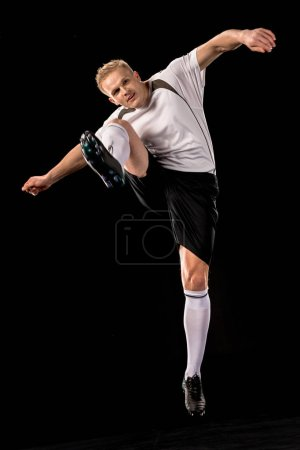 Photo for Soccer player in white and black uniform ready to shoot a ball - Royalty Free Image