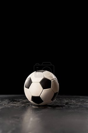 Photo for Single soccer ball on black floor - Royalty Free Image