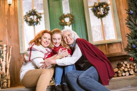 Photo pour Famille heureuse depuis trois générations, assis sur les escaliers et des caresses tout en buvant du thé chaud - image libre de droit