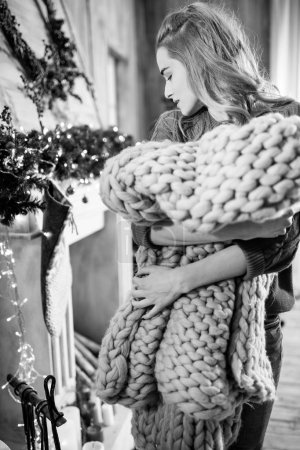 Photo for Young woman holding knitted merino wool blanket, black and white photo - Royalty Free Image