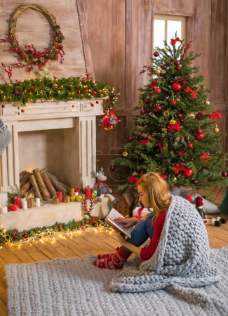 Photo for Thoughtful young woman sitting on carpet and reading book at christmastime - Royalty Free Image
