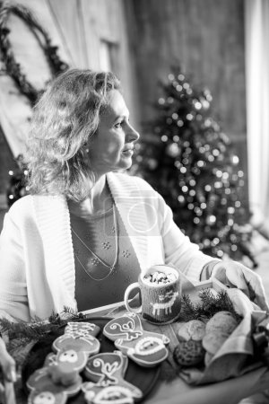 Photo for Smiling woman holding tray with christmas cookies and looking away, black and white photo - Royalty Free Image