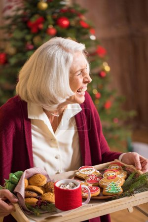Photo for Laughing mature woman holding tray with christmas cookies and hot drink - Royalty Free Image