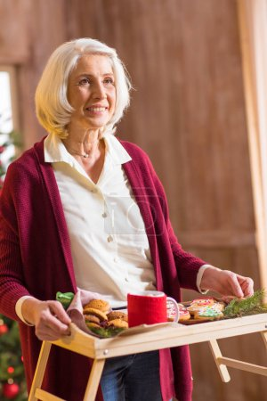 Woman holding tray with christmas cookies