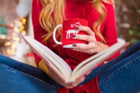 Photo for Close-up partial view of young woman reading book and holding cup with hot drink - Royalty Free Image