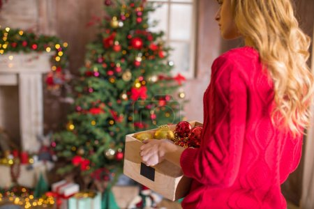 Photo for Young blonde woman holding box with shiny baubles - Royalty Free Image