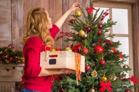 Photo for Young blonde woman decorating christmas tree with shiny baubles - Royalty Free Image