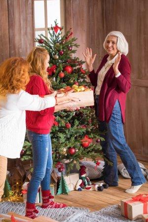 Photo pour Joyeux famille de trois générations décorant l'arbre de Noël - image libre de droit