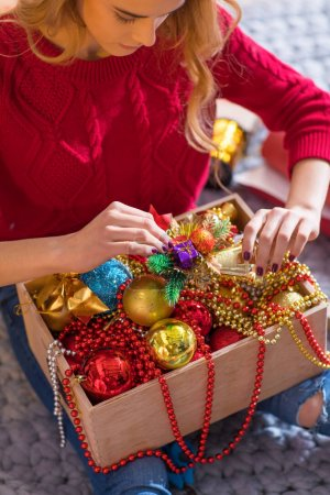 Photo for Young blonde woman holding box with shiny baubles and christmas decorations - Royalty Free Image