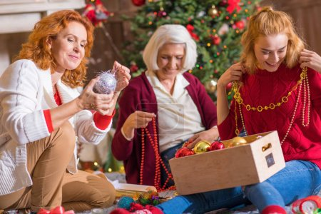 Photo for Happy family from three generations having fun with christmas decorations - Royalty Free Image