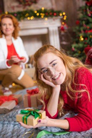 Smiling girl holding gift box