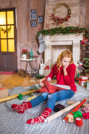 Photo for Thoughtful girl sitting on grey carpet with rolls of wrapping paper and looking at christmas presents - Royalty Free Image