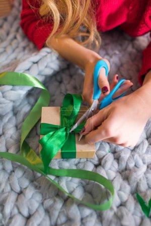 Photo pour Gros plan vue partielle de la jeune fille allongée sur le tapis et emballage boîte-cadeau - image libre de droit