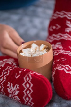 Female feet and cup with hot chocolate