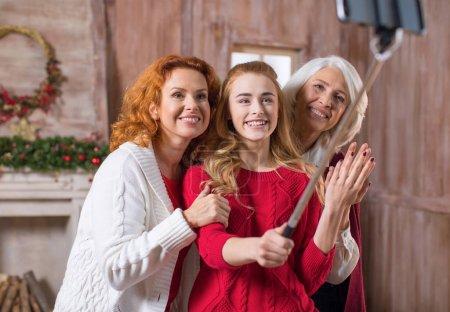 Foto de Familia feliz de tres generaciones haciendo selfie delante de decoración para chimenea de Navidad - Imagen libre de derechos