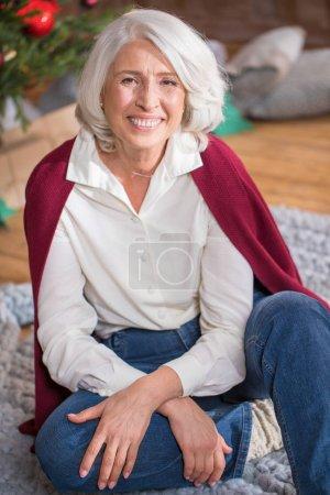 Foto de Mujer senior sonriente sentada en el suelo y mirando a la cámara - Imagen libre de derechos