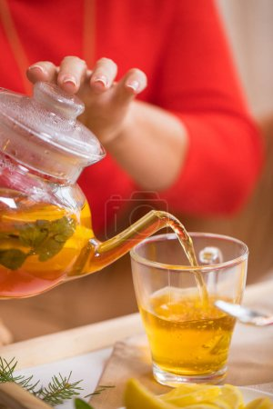 Photo for Woman sitting on the floor and pouring lemon tea in glass cups - Royalty Free Image