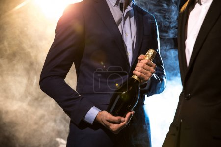 Photo for Partial view of two stylish men in suits with champagne bottle - Royalty Free Image