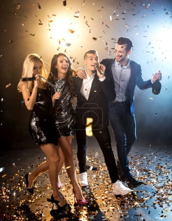 Photo for Group of happy stylish friends celebrating with champagne bottle and confetti - Royalty Free Image