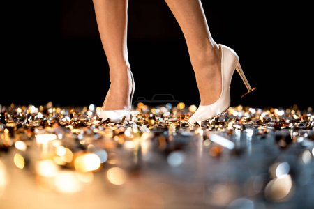 Photo for Slim female legs in high-heeled shoes standing on golden confetti - Royalty Free Image