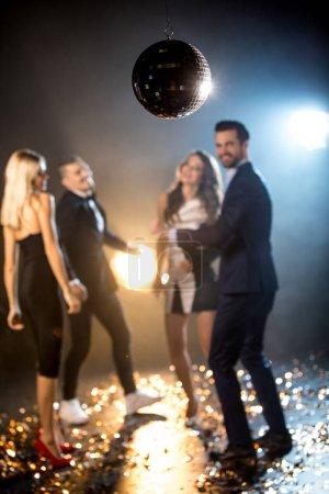 Photo pour Heureux amis élégants danser en discothèque - image libre de droit