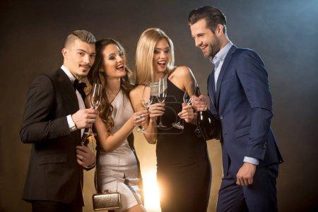 Photo pour Heureux jeunes amis élégants boire du champagne tout en célébrant - image libre de droit