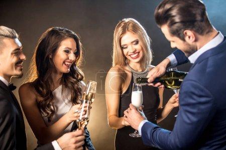 Photo pour Heureux jeunes amis élégants buvant du champagne - image libre de droit