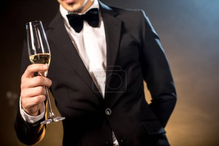Partial view of young man in tuxedo holding champa...