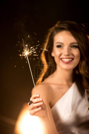 Photo pour Beautiful brunette woman holding sparkler and celebrating - image libre de droit