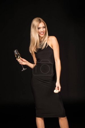 Photo for Gorgeous blonde woman in black dress holding champagne glass and macaroon isolated on black - Royalty Free Image