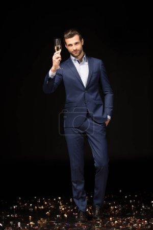 Photo pour Jeune homme célébrant tenant verre de champagne isolé sur noir - image libre de droit