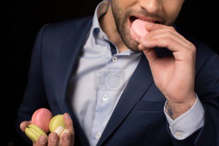 Photo for Partial view of young man eating macaron isolated on black - Royalty Free Image