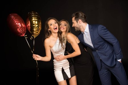 Photo pour Heureux amis à la fête avec des ballons d'air isolés sur noir - image libre de droit