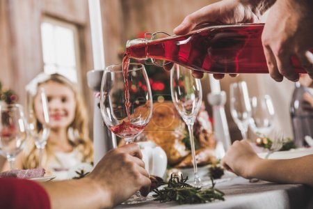 Photo for Close-up partial view of man pouring wine in glass at Christmas eve - Royalty Free Image