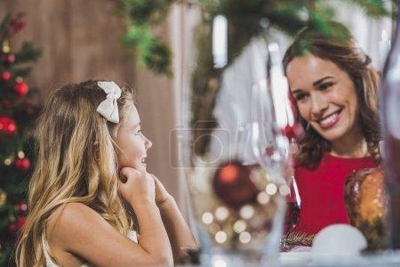Photo pour Joyeux mère et fille assis à la table de vacances à Noël - image libre de droit