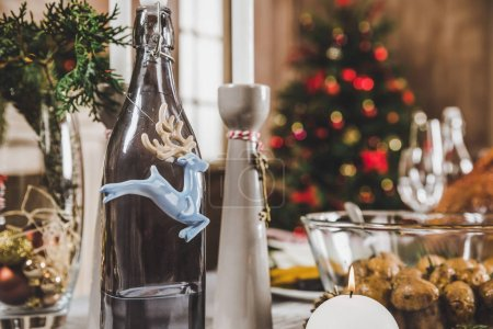 Photo for Close-up view of decorated bottle and Christmas decorations on festive table - Royalty Free Image