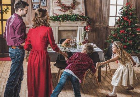 Photo pour Vue arrière de la famille heureuse se tenant la main et s'amusant à la veille de Noël - image libre de droit