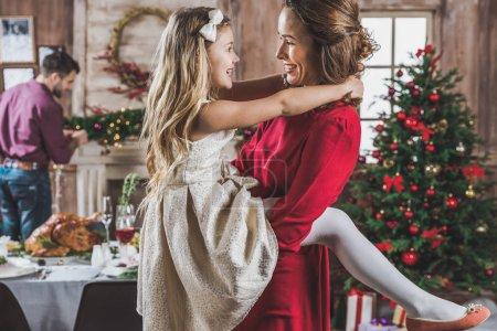 Photo pour Mère et fille heureuses s'embrassant et se regardant la veille de Noël - image libre de droit