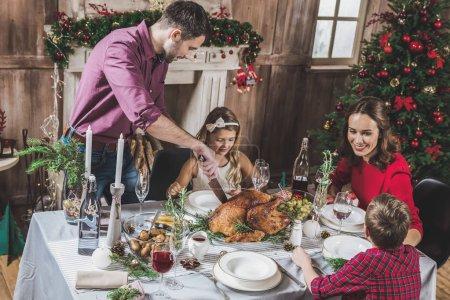 Photo pour Bonne famille de quatre personnes ayant rôti la dinde pour le dîner de Noël - image libre de droit