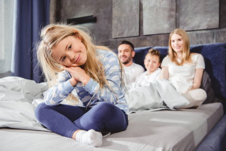 Photo for Happy little girl sitting on bed with her family and looking at camera - Royalty Free Image