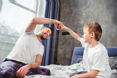 Photo for Happy father and son touching fists in bedroom - Royalty Free Image