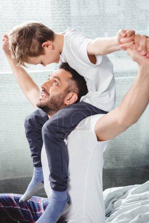 Photo pour Heureux père portant son fils souriant sur le cou et l'autre en regardant dans la chambre - image libre de droit