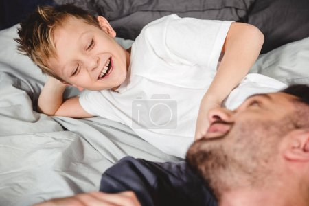 Happy father and son on bed