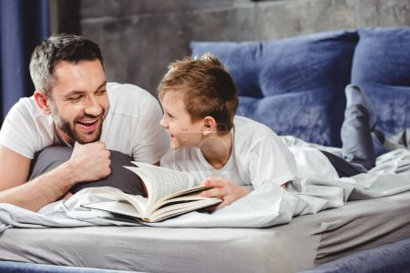 Photo for Smiling father and son reading book in bed - Royalty Free Image