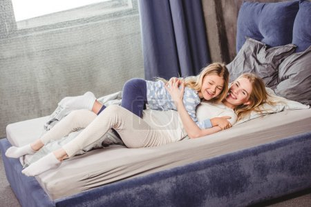 Photo for Happy mother and daughter in pajamas lying and having fun in bed - Royalty Free Image