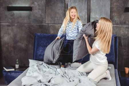 Mother and daughter fighting with pillows