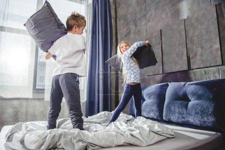 Photo pour Jolis frères et sœurs souriants se battant avec des oreillers sur le lit dans la chambre - image libre de droit