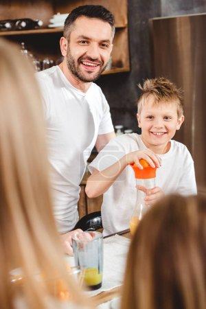 Photo pour Petit garçon et son père font de jus d'orange pour le petit déjeuner - image libre de droit
