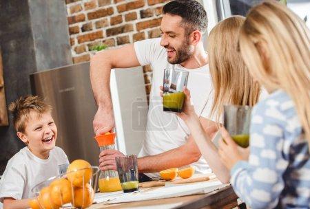 Photo pour Jeune homme fait le jus d'orange pour sa famille pour le petit déjeuner - image libre de droit